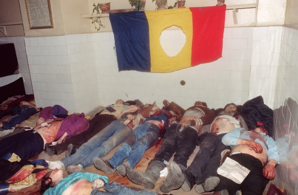 The bodies of people killed in the fightings at the Royal Palace Square are seen in the morgue of an emergency hospital in Bucharest on December 24, 1989, underneath a Romanian flag with the communist party cut out as the anti-Communist uprising to end Nicolae Ceausescu's 24 years of dictatorial rule continue. (Photo credit should read /AFP/Getty Images)